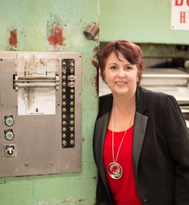 Nicole Stewart standing alongside one of the older pieces of equipment in her factory.